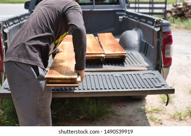 Carpenter uploading pile of lumber woods and palnks on to pick up truck. Woodworking concept.