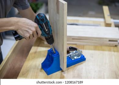 Carpenter use drilling machine with blue pocket hole jig, dowel jig, drill hole on wooden plate