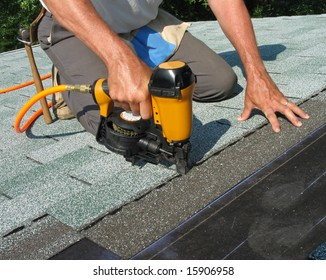 Carpenter uses nail gun to attach asphalt shingles to roof