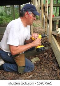 Carpenter uses screw gun to rebuild stairs to deck