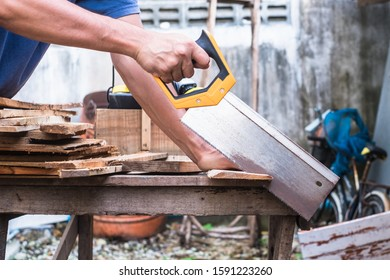 Carpenter using backsaw hand tool cutting wood plank at outdoor workshop.
