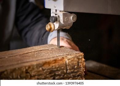 Carpenter Using Bandsaw To Cut Old Reclaimed Oak Wood Beam