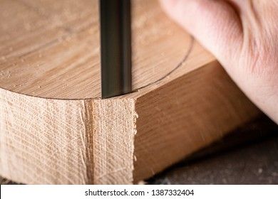 Carpenter Using A Bandsaw To Precisely Cut Piece Of Oak Wood For Furniture On Carpentry Table