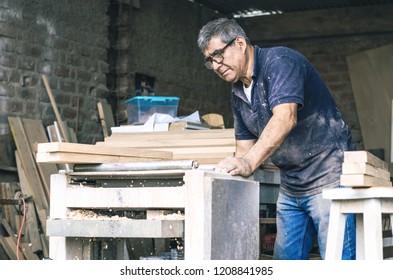 Carpenter using belt sander. Carpenter sanding a wood with belt sander