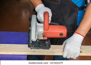 Carpenter Using Circular Saw for wood on wooden table