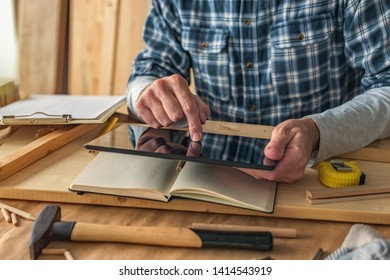 Carpenter using digital tablet to complete project to do list in small business woodwork workshop