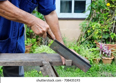 Carpenter using dovetail saw to cut the wooden stick