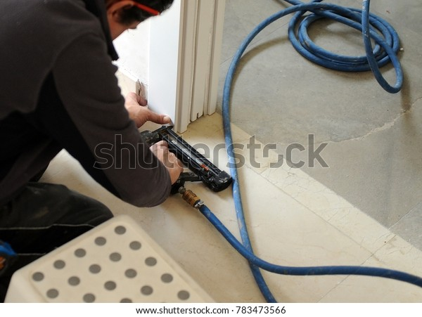 Carpenter using an electric compressed air tool for inserting nails in the assembly of a sliding door