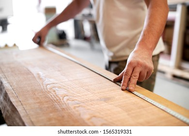 Carpenter using a measuring tape in a workshop to measure the length of a plank of wood with selective focus to his hand