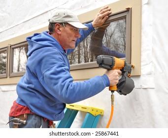 Carpenter using nail gun to install trim around windows