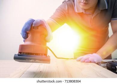 Carpenter using sander machine sanding on pine wood surface