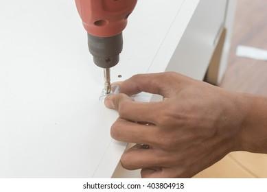 carpenter using Screwdriver assemble furniture