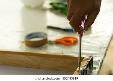 Carpenter using a screwdriver with hanging picture frames, Selective focus and small depth of filed.