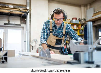 Carpenter using woodworking tools for craft work in carpentry workshop