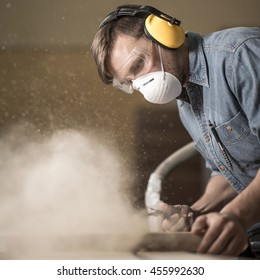 Carpenter wearing protective headphones while using electric saw