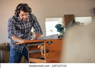 Carpenter wearing safety gear sawing a piece of wood with a table saw while working alone in his woodworking studio