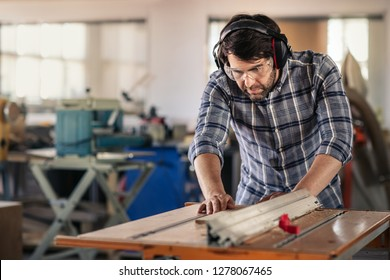 Carpenter wearing safety gear using a table saw to cut a plank of wood while working in his woodworking studio
