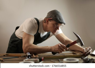 A carpenter wearing a white hard hat working with a hammer and screws trying to fix a wooden table