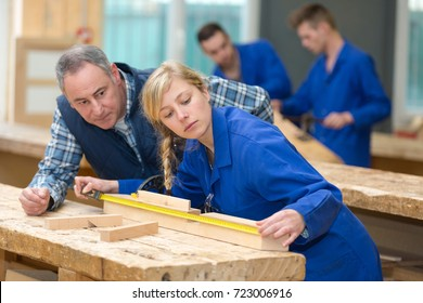 carpenter woman and man with in wood workshop