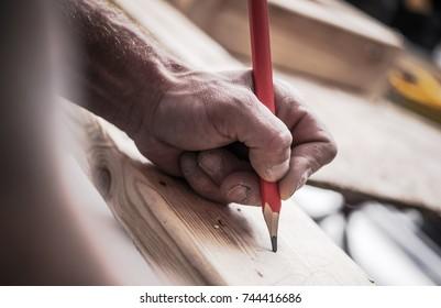 Carpenter Woodwork Job. Contractor Hand with Pencil Closeup Photo.
