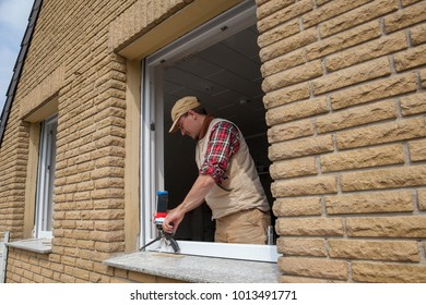 carpenter at work after replacing the windows using silicone sealant