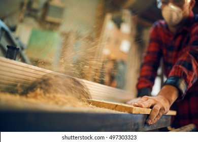 Carpenter at work at his workshop, focus on his hand