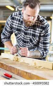 Carpenter work with planer on wood plank in workshop
