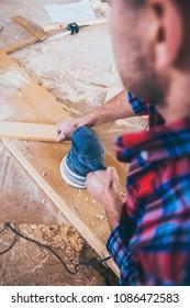Carpenter At Work Polishing Wood Using Orbit Sander