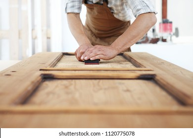 carpenter work the wood with the sandpaper