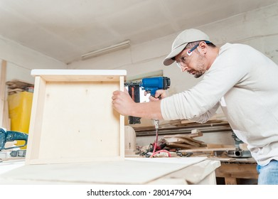 Carpenter working assembling a drawer with a screwdriver, he is wearing safety glasses protection