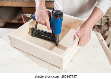 Carpenter working assembling a drawer with a screwdriver.