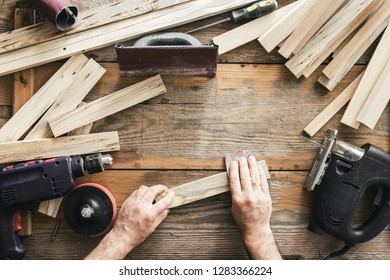 Carpenter working in carpentry workshop. Man sanding manually plank top view