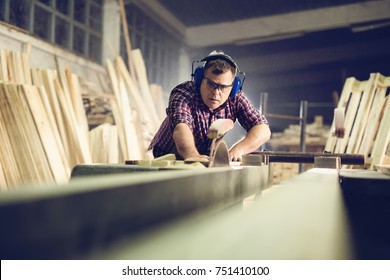 Carpenter working with circular saw at carpentry workshop