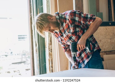 carpenter working with a drill on a wooden table