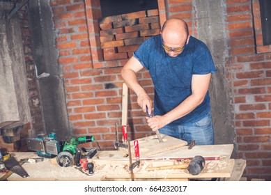 Carpenter working with hand tool.