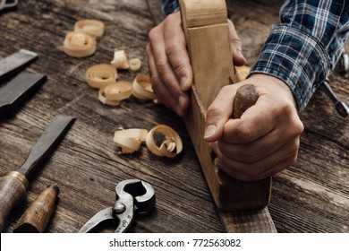 Carpenter working in his workshop, he is smoothing a wooden board using a planer, carpentry, carpentry, woodworking and craftsmanship concept