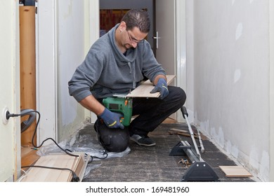 Carpenter working in a narrow passage sanding and cutting new floor boards to be installed during renovations after removing the old floor tiles