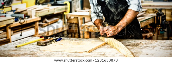 Carpenter working on his craft in dusty workshop