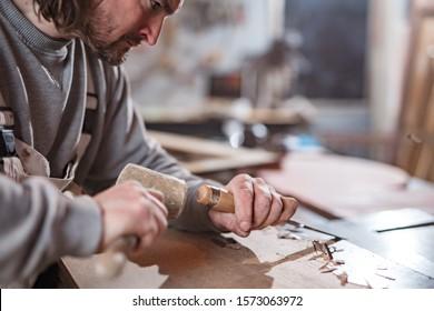 Carpenter working on a old wood in a retro vintage workshop.