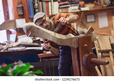Carpenter working on wooden item in workshop, taking measurements. Half-length profile portrait of a man in glasses, sweater and a cap, with blurred background and copy space.