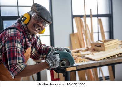 Carpenter working on woodworking machines in carpentry shop, wooden product