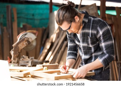 Carpenter working on woodworking machines in carpentry shop. A man works in a carpentry shop.