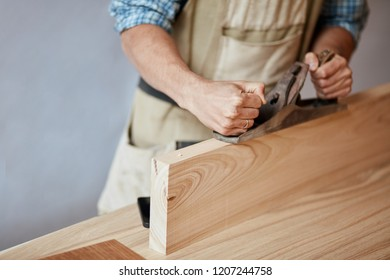 carpenter working with plane on wooden background,