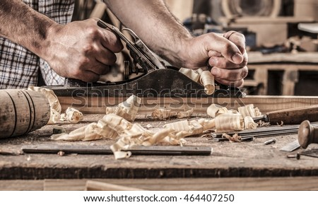 carpenter working with plane on wooden background