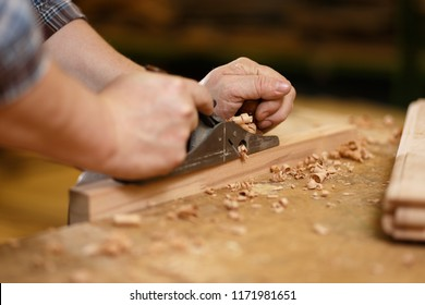 Carpenter working with planer on the workbench