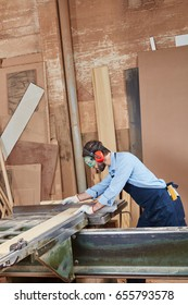 Carpenter working with saw and processing wood