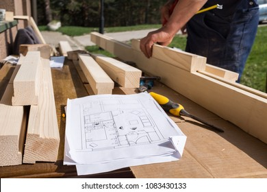 Carpenter working with technical drawing or blueprint construction paper lying on a workshop outdoor desk, surrounded with carpentry tools and wood, furniture making or house renovation process