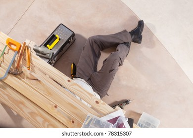 Carpenter working under the table with carpentry tools around