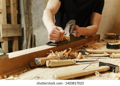 Carpenter working a wooden board with a plane