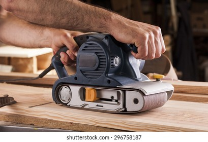 carpenter works with belt sander in carpentry